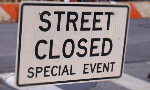A street sign, announcing a special event street closure.